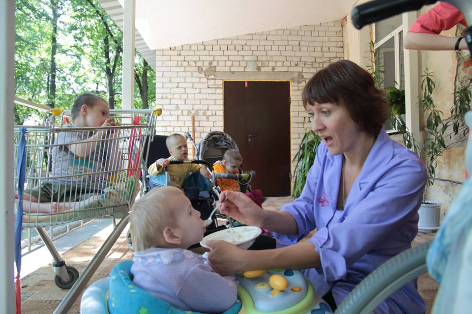 Няня-кормит-малыша-на-веранде
